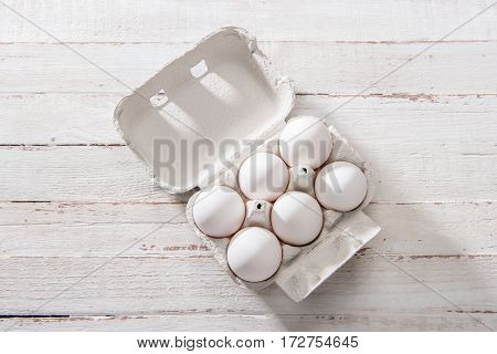 Top view of raw chicken eggs in open egg box on white wooden table