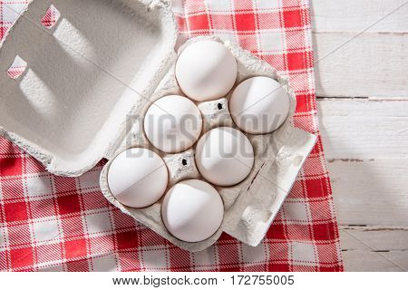 Close-up top view of raw chicken eggs in egg box on checkered tablecloth