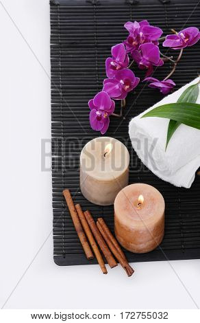 Spa setting with branch orchid, towel, cinnamon, candle,mat,lesaf