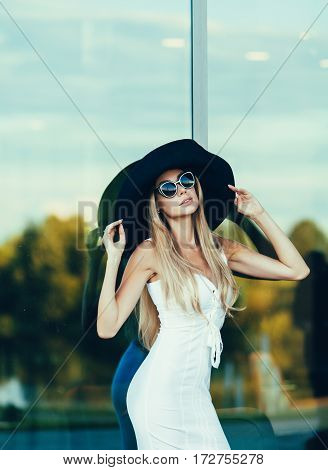 Portrait of beautiful sexy fashion woman model in summer hat and in white dress posing in summer day.
