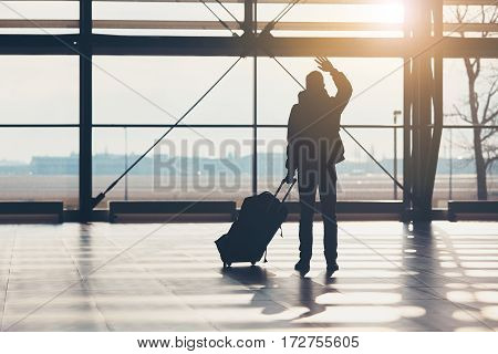 Saying goodbye at the airport. Silhouette of the traveler waves his hand.