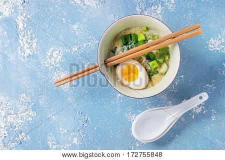 Bowl with asian style soup with scrambled eggs, half of marinated egg, spring onion, spinach served with wood chopsticks and spoons over blue texture concrete background. Top view with space