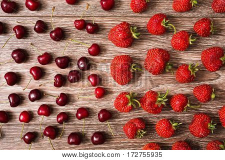 Ripe juicy red cherry and a big red strawberry lying on a wooden background. Sweet summer berries. Flat lay berries. Top view of cherry.