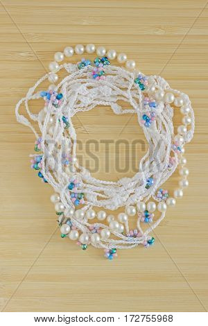 Handmade crocheted cotton organic lace wreath. White knitted frame pattern handicraft background needlework creative craft. Tender crochet wreath with pearls beads place for text