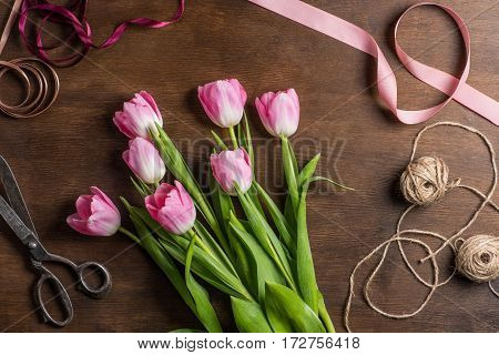 top view of beautiful pink tulips on wooden table with ribbons ropes and old scissors for making bouquet
