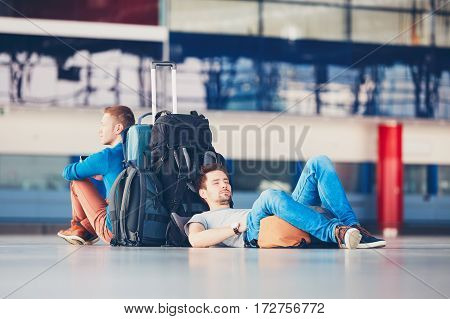 Two friends traveling together. Travelers waiting at the airport departure area for their delay flight.