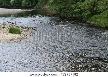 A Shallow River Flowing Past a Rocky Island.