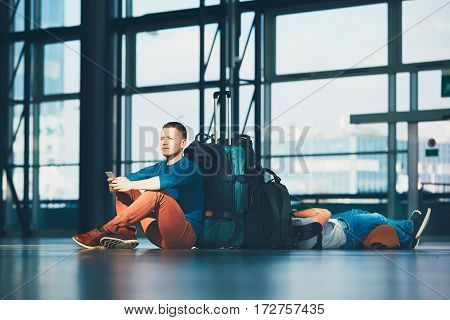 Two friends traveling together. Travelers waiting at the airport departure area for their deley flight.