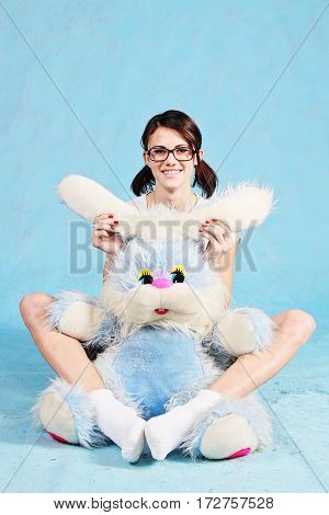 Beautiful smiling girl in glasses sits with a soft toy rabbit isolated on a blue background.