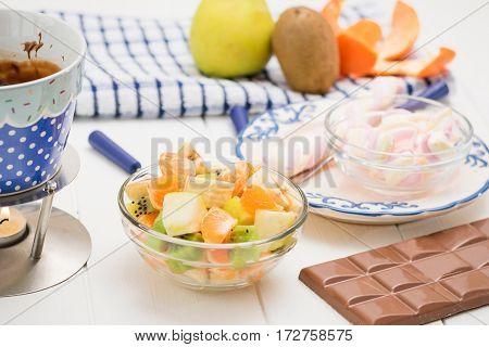 Fondue chocolate marshmallows apple tangerine kiwi and banana. Homemade holiday dish. Children's party.