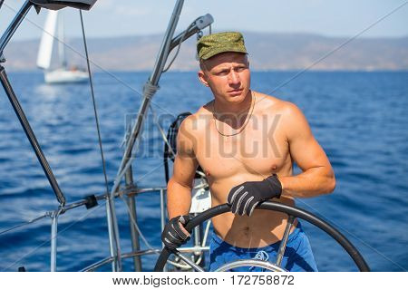 Man skipper at the helm controls of a sailing yacht during sea boats race.