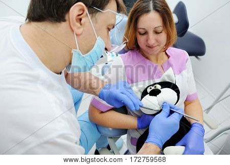 Male dentist and assistant girl examine teeth toy cat. Student medic dentist take an examination on a patient toy.toy black cat in the dental chair