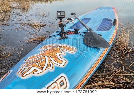 FORT COLLINS, CO - FEBRUARY 18, 2017: Paddling and video making - GoPro Hero 5 camera mounted with a suction cup on a bow of Starboard stand up paddleboard with Quickblades paddle..