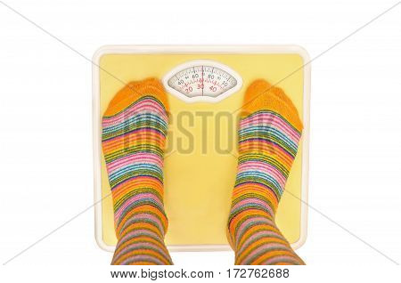 legs in color pantyhose stand on the scales isolated on white background