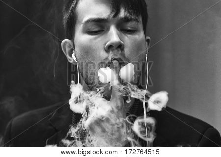 Young Handsome White Guy Let Rings Out Of Steam. Vaping. Electronic Cigarette. Black And White Photo