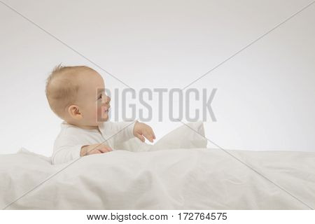Laying funny baby boy on the white blanket. Studio shot. Isolated.