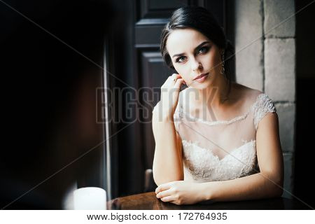 Attractive brunette bride in wedding white dress, looking at camera, portrait, copy space.
