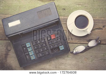 old calculator and coffee on the wooden table