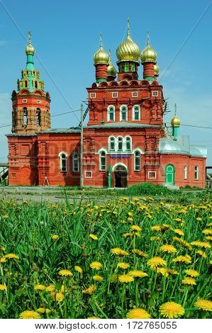 Temple for sake of Saint Nikolay Chudotvorts behind dandelion flowers. Kulakovo. Tyumen region. Russia