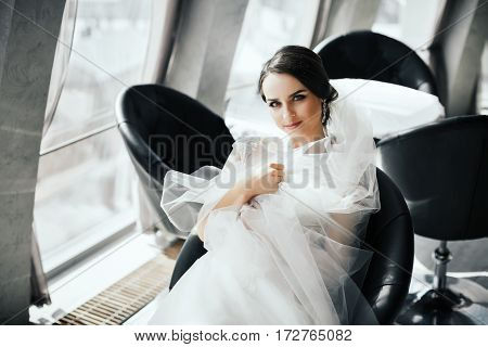 Beautiful brunette bride in wedding white dress, looking at camera and smiling, portrait, copy space.