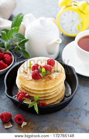 Stack of fluffy buttermilk pancakes with raspberry and coconut for breakfast