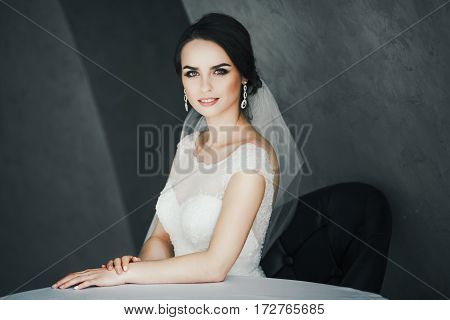 Gorgeous bride sitting in white dress at gray background, looking at camera and smiling, portrait.
