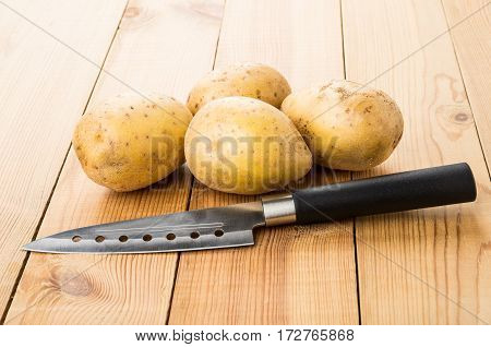 Heap Raw Potatoes And Kitchen Knife On Table