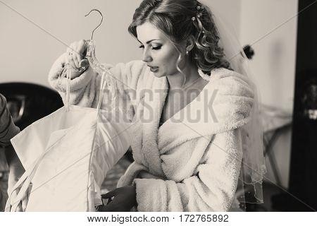 Bride In A Bathrobe Prepares To Put On A Wedding Dress