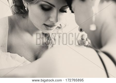 Bride Looks Down Standing Head To Head With A Bridesmaid
