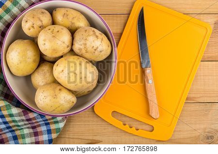 Bowl With Raw Potatoes, Towel, Chopping Board And Knife