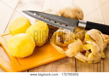Peeled Raw Potatoes And Paring On Cutting Board And Knife