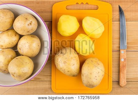 Peeled Raw Potatoes On Cutting Board, Glass Bowl