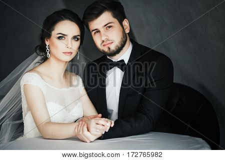 Lovely wedding photo, brunette bride and bridegroom sitting together at gray background and holding hands.