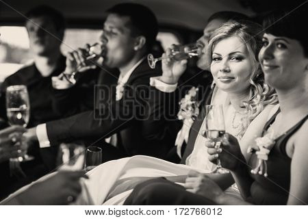 Just Married Couple And Their Friends Drink Champagne In The Limousine