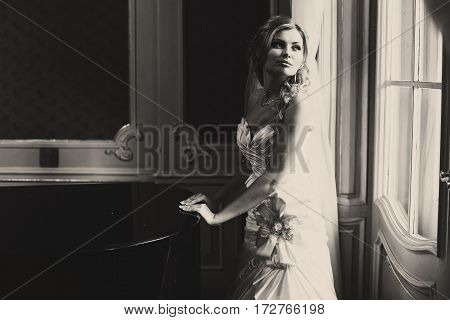 Bride Stands In The Daylight Behind A Piano