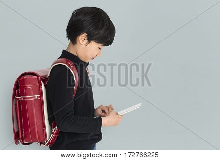 Young asian kid with a backpack using a tablet isolated portrait