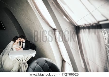 Attractive bride and bridegroom standing close to each other at big window at background, wedding photo.