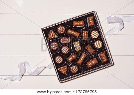 Top View Of Various Chocolate Pralines In Box On White Wooden Background.