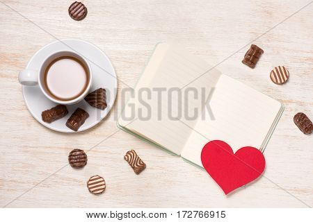 Valentines Day Background With Chocolate Balls, Coffee Cup, Red Hearts And Notebook
