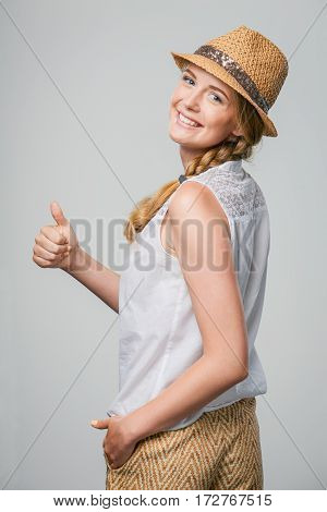Beautiful smiling woman wearing summer straw fedora hat looking at camera over shoulder and gesturing thumb up