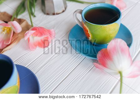 Pink tulips and coffee cups. Mother`s Day or Women`s Day on a white background