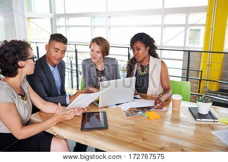 Candid photo of a corporate businesspeople group discussing strategies in professionnal indoors setting. poster