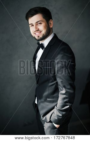 A portrait of handsome bridegroom standing at gray background, looking at camera and smiling, copy space.