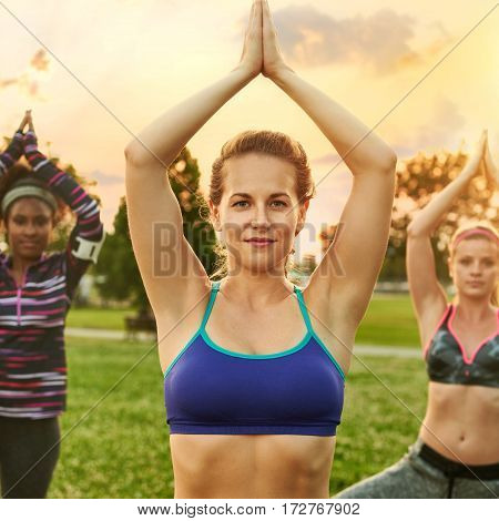 Yoga fitness coach leading her group into a lotus pose with the sunlight behind. Sunset golden tone filter