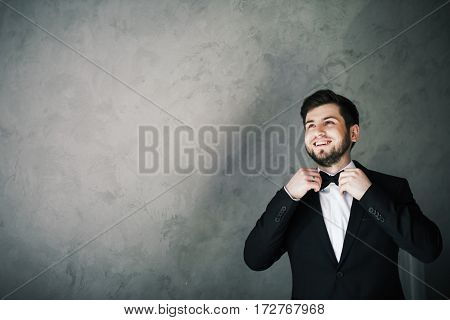 Handsome bridegroom standing at gray background, looking left and smiling, copy space.