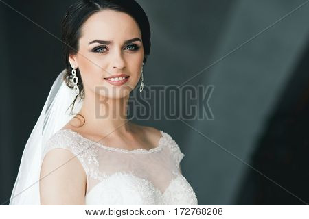 Gorgeous bride in white dress at gray background, looking at camera and smiling, portrait.