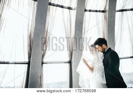 Beautiful brunette bride and bridegroom standing close to each other at big window at background, wedding photo, copy space.