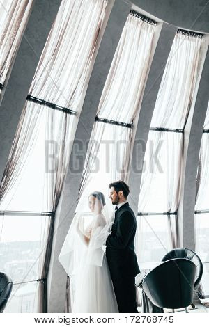 Attractive brunette bride and bridegroom standing close to each other at big window at background, wedding photo.