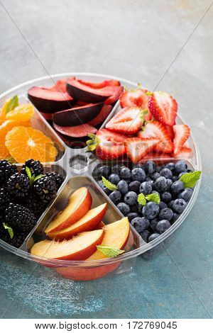 Assorted fruit and berries on a plate with strawberry, peaches, blackberry and orange