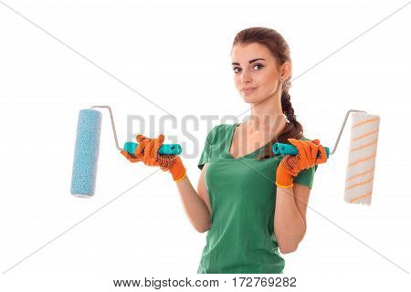 young beauty brunette woman builder in uniform with paint roller in hands make reovations isolated on white
